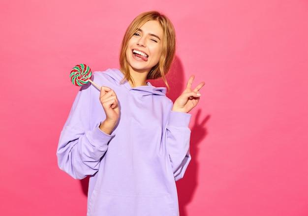 Retrato de mulher jovem bonita sorridente hipster com capuz na moda verão. mulher despreocupada sexy posando perto de parede rosa. modelo positivo com pirulito piscando