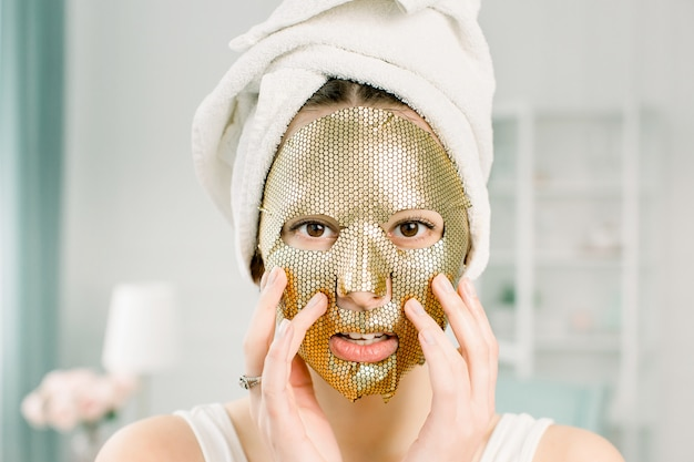 Retrato de mulher jovem bonita toalha branca na cabeça com máscara de ouro folha cosmética no rosto de beleza. conceito de cuidados com a pele