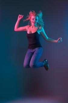 Retrato de mulher jovem caucasiana em fundo gradiente em luz de néon. linda modelo feminino com aparência incomum. conceito de emoções humanas, expressão facial, vendas, anúncio. pulando, sorrindo.