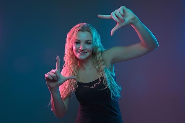 Retrato de mulher jovem caucasiana em fundo gradiente em luz de néon. linda modelo feminino com aparência incomum. conceito de emoções humanas, expressão facial, vendas, anúncio. sorrindo fofo.