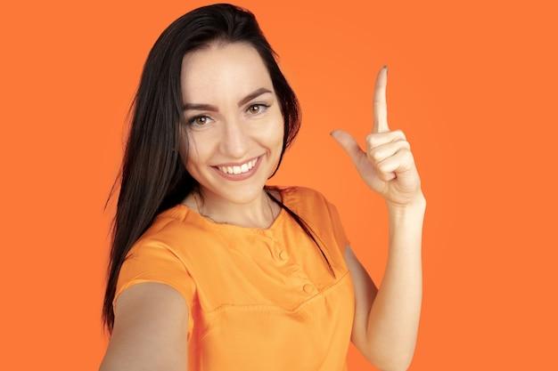 Retrato de mulher jovem caucasiana em fundo laranja do estúdio. bela morena modelo feminino na camisa. conceito de emoções humanas, expressão facial, vendas, anúncio. copyspace. apontando, mostrando, sorrindo.