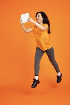Retrato de mulher jovem caucasiana em fundo laranja do estúdio. bela morena modelo feminino na camisa. conceito de emoções humanas, expressão facial, vendas, anúncio. copyspace. pulando com o tablet.