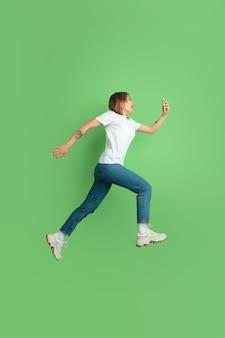 Retrato de mulher jovem caucasiana na parede verde do estúdio