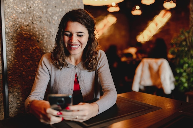 Retrato de mulher jovem caucasiana sorridente em um restaurante segurando e usando um smartphone.