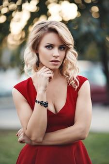 Retrato de mulher jovem caucasiano sexy vestido vermelho com longos cabelos loiros