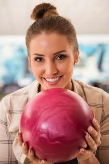 Retrato de mulher jovem com bola de boliche rosa