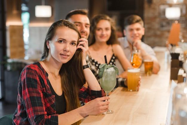 Retrato, de, mulher jovem, com, dela, amigos, sentando, em, barra, contador, segurando, bebidas