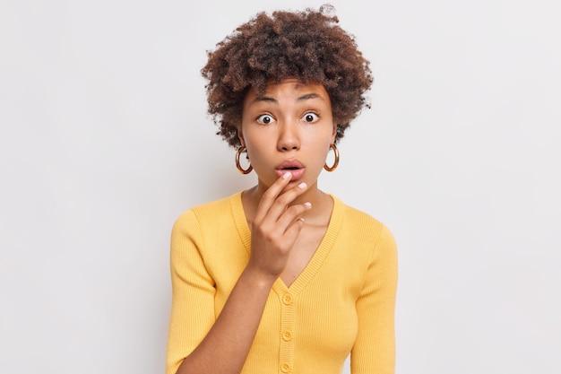 Retrato de mulher jovem com expressão de espanto levanta sobrancelhas segura a respiração vestida de suéter amarelo não consegue acreditar que seus olhos estão isolados sobre a parede branca