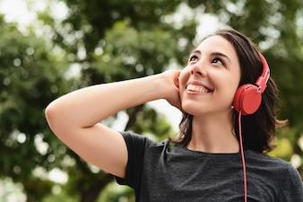 Retrato, de, mulher jovem, com, fones vermelhos, escutar música