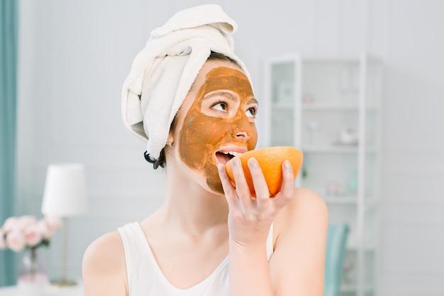 Retrato de mulher jovem com máscara de argila no rosto segurando fatias de limão e toranja, cuidados faciais