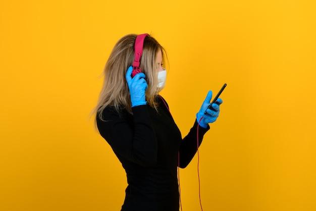 Retrato de mulher jovem com máscara e fones de ouvido