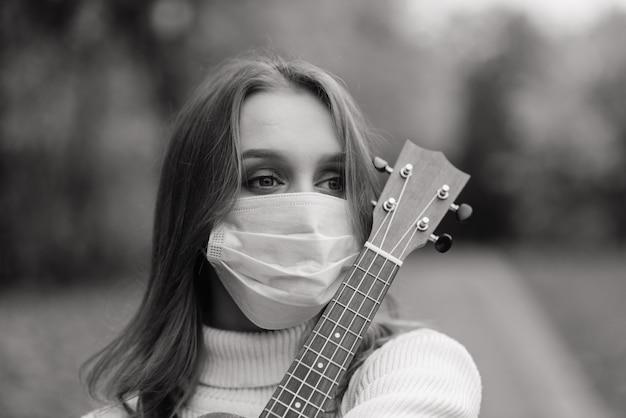 Retrato de mulher jovem com máscara protetora tocando guitarra ukulele no parque outono, conceito de viagem saudável