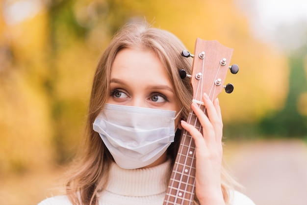 Retrato de mulher jovem com máscara protetora tocando guitarra ukulele no parque outono, conceito de viagens saudáveis de estilo de vida