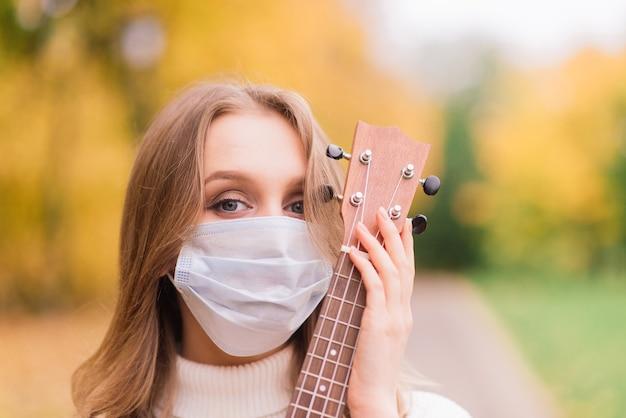 Retrato de mulher jovem com máscara protetora tocando guitarra ukulele no parque outono, conceito de viagens saudáveis de estilo de vida Foto Premium
