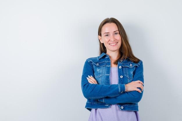 Retrato de mulher jovem com os braços cruzados na jaqueta jeans e olhando alegre para a frente