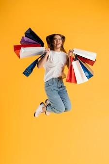 Retrato de mulher jovem com sacolas de compras pulando