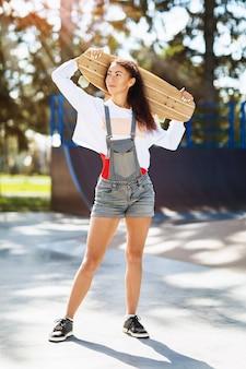 Retrato de mulher jovem com um longboard nas mãos no parque em uma manhã ensolarada de verão