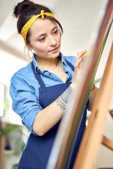 Retrato de mulher jovem concentrada em avental criando pintura abstrata em cavalete aplicando tinta