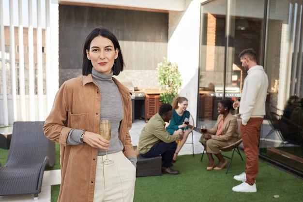 Retrato de mulher jovem contemporânea sorrindo enquanto está no terraço durante uma festa ao ar livre,