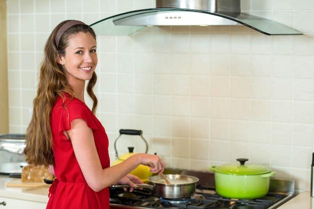 Retrato, de, mulher jovem, cozinhar, ligado, fogão, em, cozinha, casa