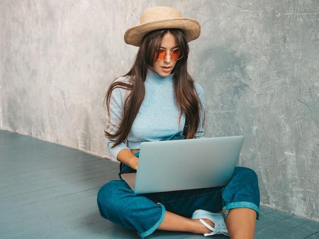 Retrato de mulher jovem criativa em óculos de sol. linda garota sentada no chão perto da parede cinza.