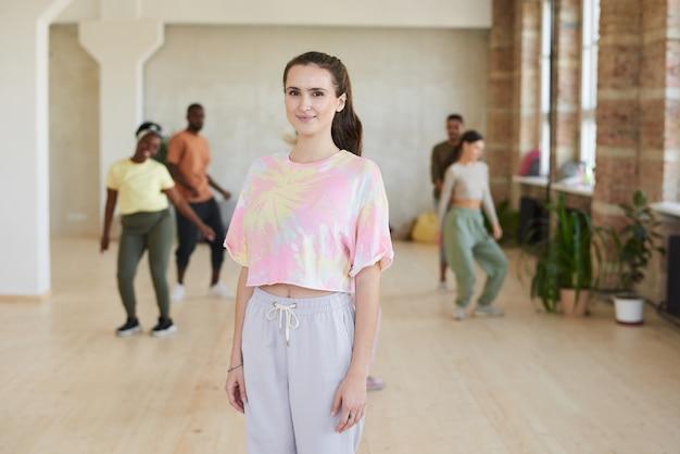 Retrato de mulher jovem dançando com outras pessoas no estúdio de dança