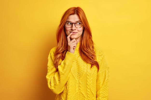 Retrato de mulher jovem de aparência agradável e satisfeita mantém o dedo indicador perto dos lábios concentrado, ao lado, tem expressão pensativa, tem cabelo ruivo natural e usa suéter casual