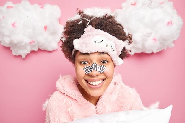 Retrato de mulher jovem de cabelos cacheados feliz aplica caminho de remoção de cravos no nariz sorrisos amplamente passa por procedimentos de cuidados com a pele de beleza vestida em poses de pijama com travesseiro e penas voando ao redor