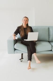 Retrato de mulher jovem de negócios com laptop sentado no sofá