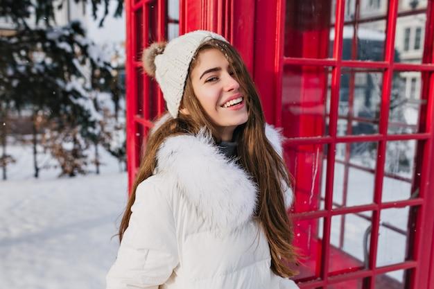 Retrato de mulher jovem e alegre com chapéu de malha quente, cabelos castanhos compridos, curtindo o tempo congelado de inverno na rua, na cabine telefônica vermelha