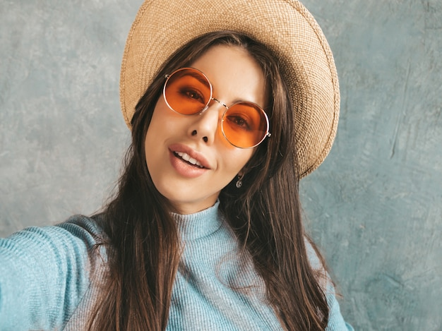 Retrato de mulher jovem e alegre, tirando foto de selfie com inspiração e usando chapéu e roupas modernas.