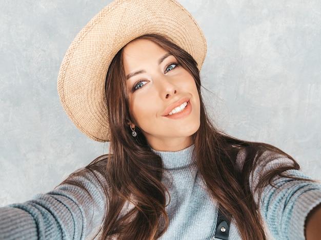 Retrato de mulher jovem e alegre tirando foto selfie e vestindo roupas e chapéu modernos.