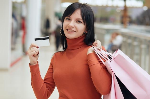 Retrato de mulher jovem e atraente caucasiano com cartão de crédito na mão com sacolas de compras,