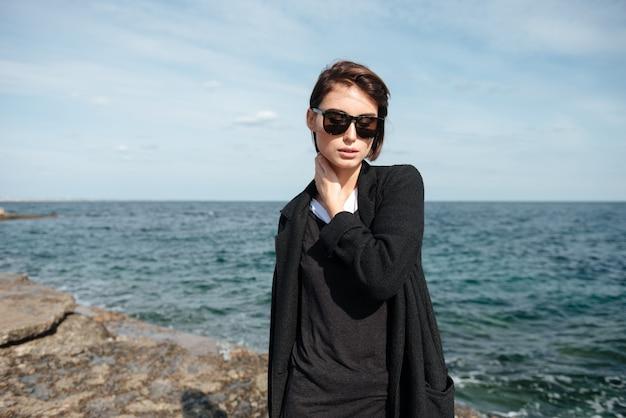 Retrato de mulher jovem e atraente com óculos escuros e casaco preto em pé perto do mar