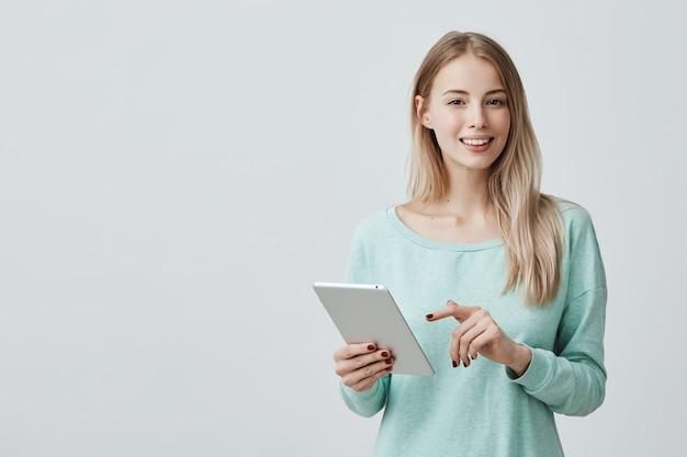 Retrato de mulher jovem e atraente com olhos escuros e cabelos loiros e compridos, vestindo blusa azul clara, trabalhando em tablet.