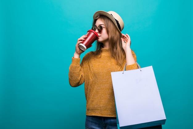 Retrato de mulher jovem e atraente com sacolas de compras e copo de papel de café fresco