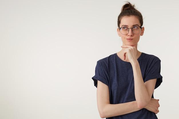 Retrato de mulher jovem e atraente de óculos olha para cima pondera um pensamento ou ideia, pensativo, mantém o punho perto do queixo, usa uma camiseta casual, sobre um fundo branco