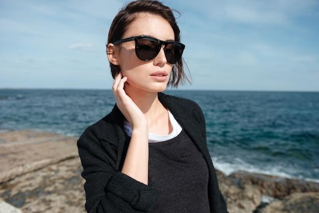 Retrato de mulher jovem e atraente em óculos de sol, caminhando perto do mar