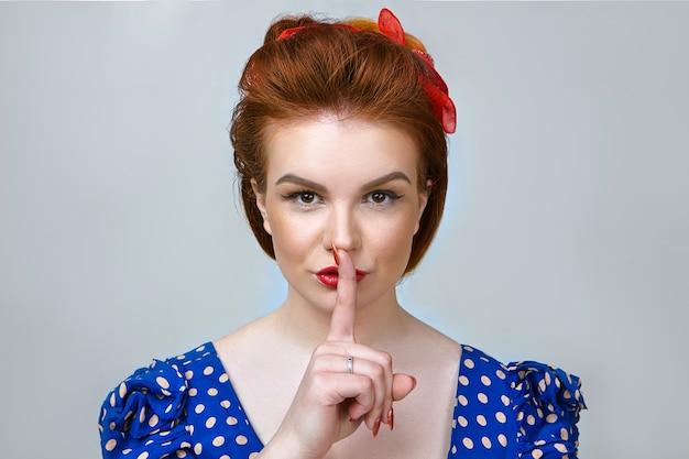 Retrato de mulher jovem e atraente em roupa retrô, ocultando informações confidenciais ou ultrassecretas, segurando o dedo indicador sobre os lábios vermelhos