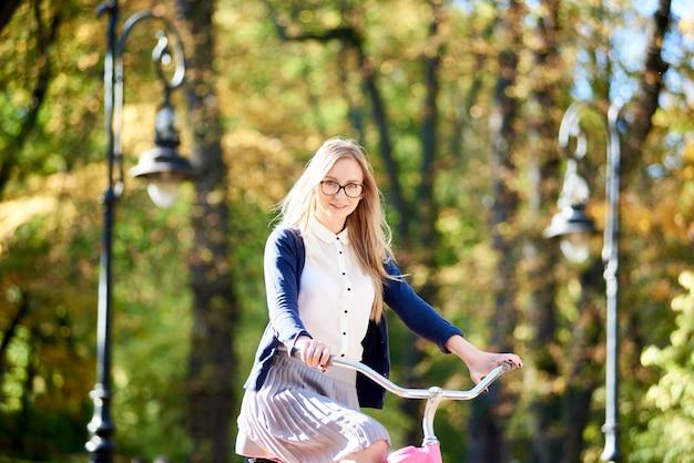 Retrato de mulher jovem e atraente feliz ciclismo bicicleta rosa senhora ao longo do beco ensolarado parque pavimentado
