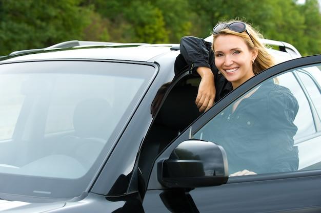 Retrato de mulher jovem e atraente feliz no novo carro - ao ar livre