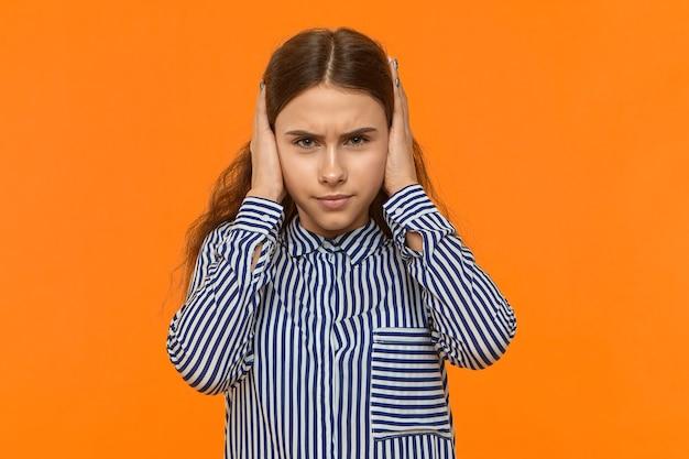Retrato de mulher jovem e atraente mal-humorada cobrindo as orelhas
