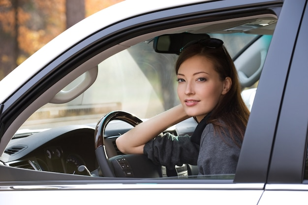 Retrato de mulher jovem e atraente no carro novo