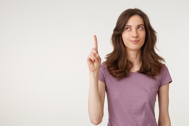 Retrato de mulher jovem e atraente olha para o canto esquerdo superior e aponta
