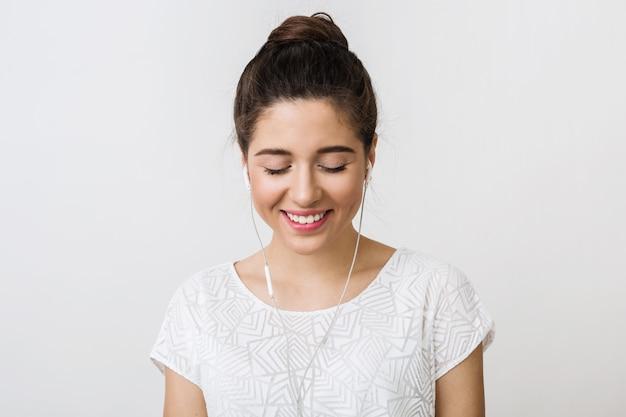 Retrato de mulher jovem e atraente ouvindo música em fones de ouvido, olhos fechados, curtindo o som, sorrindo,