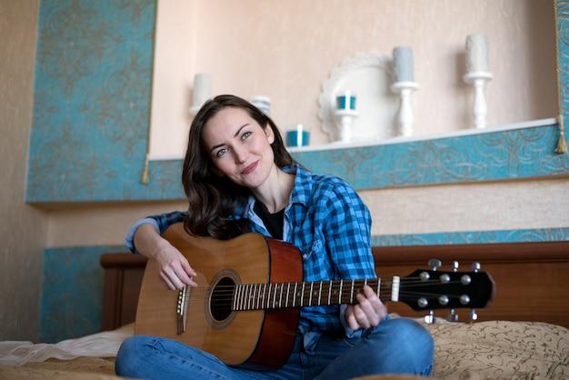 Retrato de mulher jovem e atraente sorridente com violão