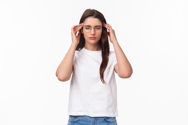 Retrato de mulher jovem e atraente tentando se preparar, massageando as têmporas com os olhos fechados,