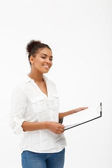 Retrato de mulher jovem e bem sucedido negócio africano sobre parede branca