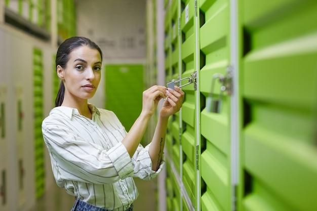 Retrato de mulher jovem e bonita abrindo o cadeado na porta da unidade de armazenamento automático e copie o espaço da cintura para cima