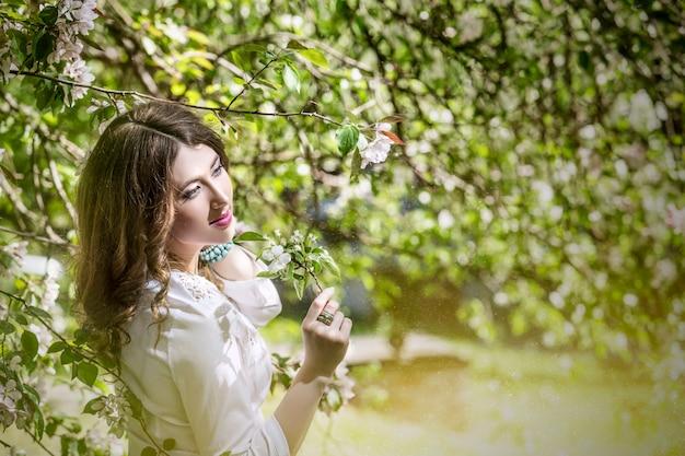 Retrato de mulher jovem e bonita ao lado de um galho de uma macieira em flor no parque ao ar livre